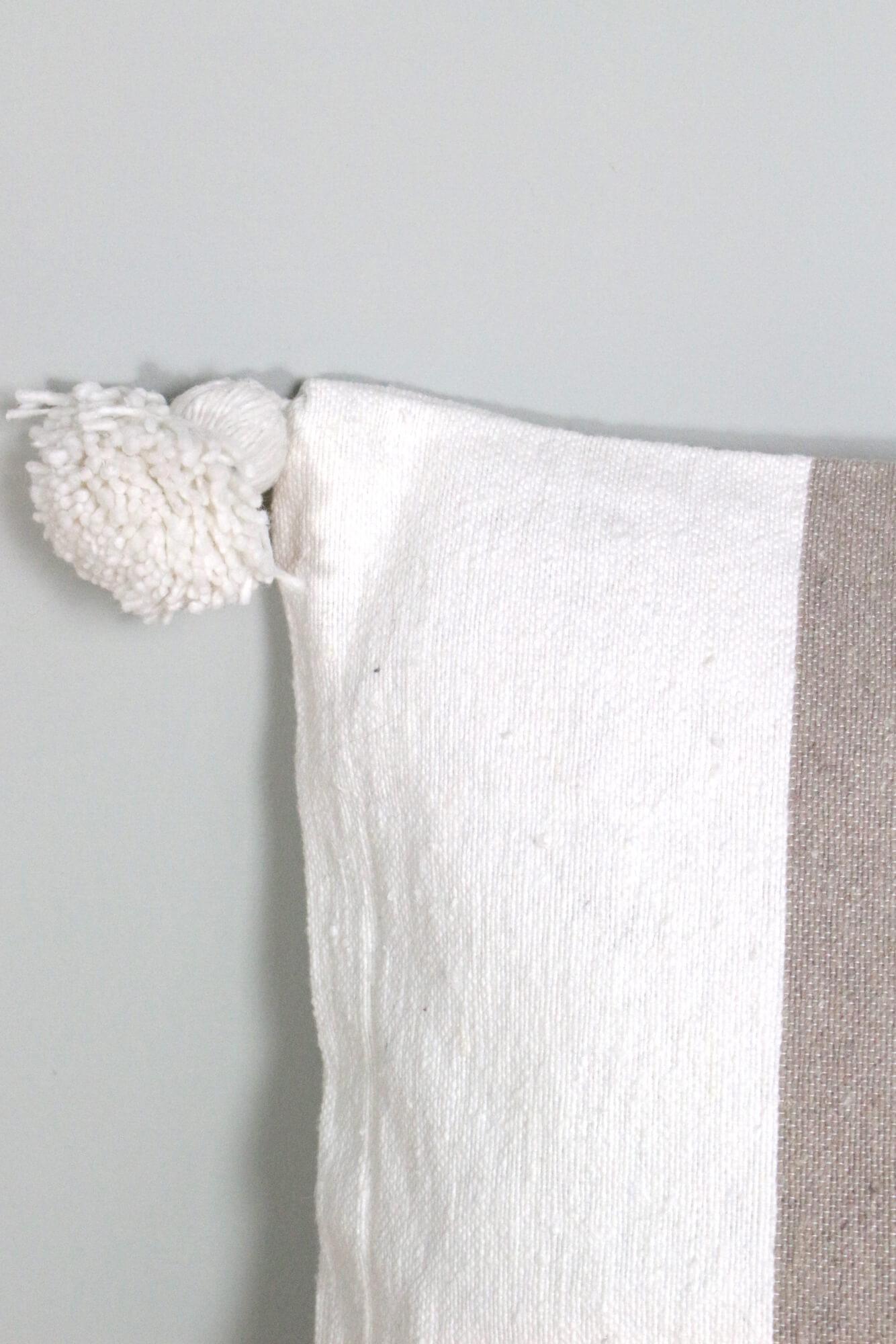 Pompom Kissen mit beigen Streifen, 50x50